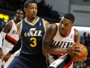 Photo - Portland Trail Blazers point guard Damian Lillard, right, drives the ball past Utah Jazz point guard Trey Burke (3) in the first half of a preseason NBA basketball game on Friday, Oct. 11, 2013, in Boise, Idaho. (AP Photo/Otto Kitsinger)