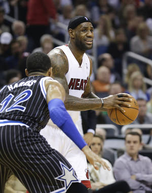 Photo - Miami Heat's LeBron James, right, looks to pass around Orlando Magic's Tobias Harris (12) during the first half of an NBA basketball game in Orlando, Fla., Saturday, Jan. 4, 2014. (AP Photo/John Raoux)