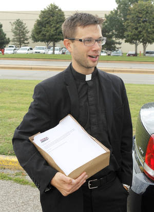 Photo - Oklahoma City clergyman Lance Schmitz holds petitions that he attempted to deliver to Hobby Lobby's corporates headquarters Thursday in Oklahoma City.  <strong>PAUL HELLSTERN - Oklahoman</strong>