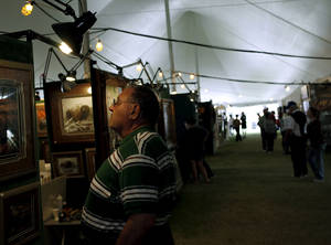 Photo - Gary Eckstein, of Norman, looks at artwork by Lane Kendrick under a tent during Arts Festival Oklahoma at Oklahoma City Community College in Oklahoma City on Sunday, September 4, 2011. Oklahoman archive photo