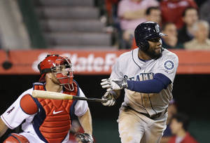 Photo - Seattle Mariners' Abraham Almonte, right, watches his RBI double during the seventh inning of a baseball game against the Los Angeles Angels on Monday, March 31, 2014, in Anaheim, Calif. (AP Photo/Jae C. Hong)
