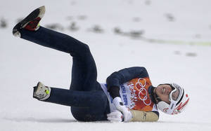 Photo - Japan's Taihei Kato holds his left arm after falling during the Nordic combined individual Gundersen large hill competition at the 2014 Winter Olympics, Tuesday, Feb. 18, 2014, in Krasnaya Polyana, Russia. (AP Photo/Gregorio Borgia)