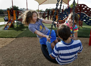 Photo - Alana Hernandez, 8, left, and Andres Garcia, 10, and his sister, Natalia, 4, play on a tire swing at a new neighborhood park adjacent to Monroe Elementary School.
