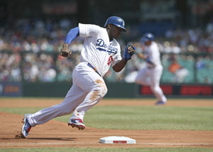 Photo - The Los Angeles Dodgers' Yasiel Puig rounds third on his way to scoring during the second game of the two-game Major League Baseball opening series between the Los Angeles Dodgers and Arizona Diamondbacks at the Sydney Cricket Ground in Sydney, Sunday, March 23, 2014. (AP Photo/Rick Rycroft)