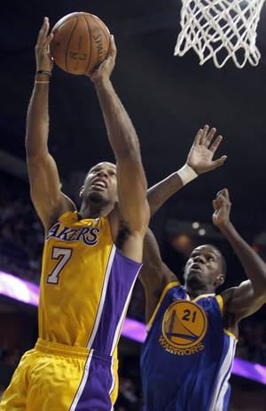 Photo - Los Angeles Lakers guard Xavier Henry (7) scores in front of Golden State Warriors center Dewayne Dedmon, right, defending in the third quarter in an NBA basketball preseason game Saturday, Oct. 5, 2013, in Ontario, Calif. Lakers won the game 104-95.   (AP Photo/Alex Gallardo)