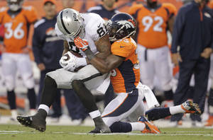 Photo - Denver Broncos strong safety Duke Ihenacho (33) pulls down Oakland Raiders tight end Mychal Rivera (81) in the first quarter of an NFL football game, Monday, Sept. 23, 2013, in Denver. (AP Photo/Joe Mahoney)
