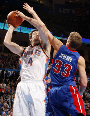 Photo - Oklahoma City's Nick Collison (4) takes the ball to the hoop as Detroit's Jonas Jerebko (33) defends during the NBA basketball game between the Detroit Pistons and Oklahoma City Thunder at the Chesapeake Energy Arena in Oklahoma City, Monday, Jan. 23, 2012. Photo by Nate Billings, The Oklahoman