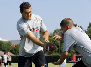 Photo - Former OU quarterback Sam Bradford works with campers in Norman.  Photo by Steve Sisney, The Oklahoman