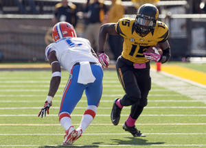 Photo - FILE - In this Oct. 19, 2013, file photo, Missouri wide receiver Dorial Green-Beckham runs as Florida Gators defensive back Marcus Roberson defends during the fourth quarter of an NCAA college football game in Columbia, Mo. Green-Beckham has been suspended indefinitely for an unspecified violation of team rules, three months after he and two friends were arrested on suspicion of felony drug distribution. Coach Gary Pinkel announced the suspension Monday, April 7, 2014, in a brief news release. (AP Photo/L.G. Patterson, File)