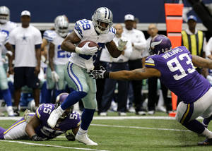 Photo - Dallas Cowboys running back DeMarco Murray (29) escapes tackle attempts by Minnesota Vikings' Marvin Mitchell (55) and Kevin Williams (93) for extra yardage in the first  half of an NFL football game, Sunday, Nov. 3, 2013, in Arlington, Texas. (AP Photo/Nam Y. Huh)