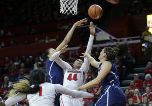 Photo - Rutgers forward Betnijah Laney (44) takes a shot as she splits Connecticut defenders Kiah Stokes and Stefanie Dolson, right, during the first half of an NCAA college basketball game Sunday, Jan. 19, 2014, in Piscataway, N.J. (AP Photo/Mel Evans)