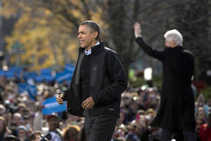 Photo -   President Barack Obama walks to the podium as former President Bill Clinton waves to the crowd at right during a campaign event in the State Capitol Square, Sunday, Nov. 4, 2012, in Concord, N.H. (AP Photo/Carolyn Kaster)