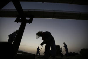 Photo -   Men work Tuesday at sunset in the desert oil fields of Sakhir, Bahrain. Dramatic changes in oil production around the globe, both higher and lower, are balancing each other out instead of wreaking havoc.  AP Photo  <strong>Hasan Jamali -  AP </strong>