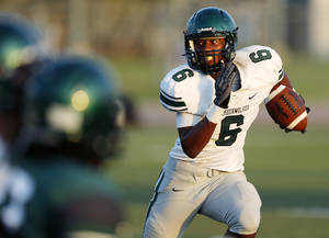 Photo - Norman North's Z'Quan Hogan (6) carries the ball against Edmond Satna Fe during a football scrimmage at Edmond Santa Fe High School in Edmond, Okla., Thursday, Aug. 22, 2013. Photo by Nate Billings, The Oklahoman