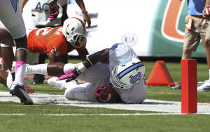 photo -   North Carolina's Giovani Bernard is stopped short of the goal by Miami Kacy Rodgers II (22) during the first half of a NCAA college football game in Miami, Saturday, Oct. 13, 2012. (AP Photo/J Pat Carter)