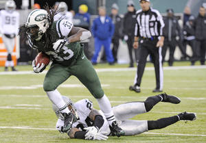 Photo - FILE - In this Dec. 8, 2013 file photo, New York Jets running back Chris Ivory (33) breaks away from Oakland Raiders safety Charles Woodson during the second half of an NFL football game, in East Rutherford, N.J. Ivory's carries the ball like a man possessed. (AP Photo/Bill Kostroun), File