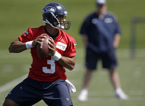 Photo -   Seattle Seahawks quarterback Russell Wilson passes during NFL football rookie minicamp, Friday, May 11, 2012, in Renton, Wash. (AP Photo/Ted S. Warren)