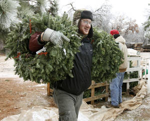 Photo - Marvin Hughey carries two bundles of wreaths Monday during the final sales day at  Sorghum Mill Christmas Tree Farm.  Photo by Paul Hellstern, The Oklahoman <strong>PAUL HELLSTERN - Oklahoman</strong>