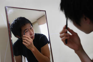 Photo -   In this Sunday, Aug. 26, 2012 photo, Cho Won-Hyuk, a 24-year-old college student, uses a black eyebrow pencil to lengthen and accentuate his eyebrows at his home Anyang, South Korea. Cho's meticulous efforts to paint the perfect face are not unusual in South Korea. This socially conservative, male-dominated country, with a mandatory two-year military conscription for men, has become the male makeup capital of the world. (AP Photo/Hye Soo Nah)
