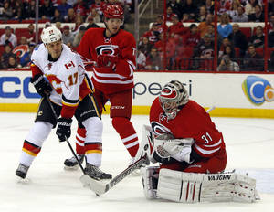 Photo - Carolina Hurricanes goalie Anton Khudobin (31) of Kazakhstan, swallows the puck in front of a charging Calgary Flames' Lance Bouma (17) and Hurricanes' Brett Bellemore (73) during the first period of an NHL hockey game in Raleigh, N.C., Monday, Jan. 13, 2014. (AP Photo/Karl B DeBlaker)
