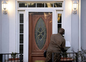 Photo - A UPS driver rings the doorbell at the home listed for Ira Curry, one of two Mega Millions lottery ticket winners that were identified by lottery officials in the $636 million drawing, Wednesday, Dec. 18, 2013, in Stone Mountain, Ga. (AP Photo/David Tulis)