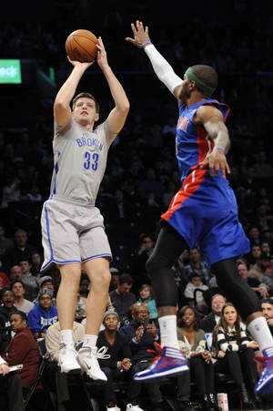 Photo - Brooklyn Nets' Mirza Teletovic (33) shoots over Detroit Pistons' Josh Smith (6) in the first half of an NBA basketball game on Friday, April 4, 2014, in New York. (AP Photo/Kathy Kmonicek)