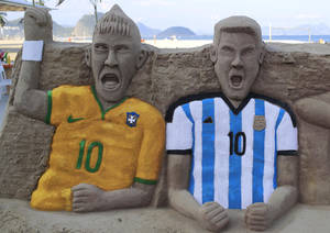 Photo - A sand sculpture featuring soccer players, Neymar of Brazil, left, and Lionel Messi of Argentina, on Copacabana beach in Rio de Janeiro, Brazil, Monday, June 2, 2014. The 2014 Brazil World Cup is set to begin in a few days, with Brazil and Croatia competing in the opening match on June 12. (AP Photo/Hassan Ammar)