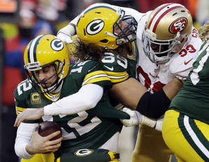 Photo - San Francisco 49ers outside linebacker Aldon Smith, right, grabs Green Bay Packers quarterback Aaron Rodgers (12) as Smith fights against the Packers offensive tackle David Bakhtiari (69) during the first half of an NFL wild-card playoff football game, Sunday, Jan. 5, 2014, in Green Bay, Wis. (AP Photo/Mike Roemer)