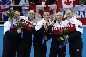 Photo - Canada's curlers, from left, Caleb Flaxey, Ryan Harnden, E.J. Harnden, Ryan Fry, and Brad Jacobs pose during flower ceremony after winning the men's curling gold medal at the 2014 Winter Olympics, Friday, Feb. 21, 2014, in Sochi, Russia. (AP Photo/Robert F. Bukaty)