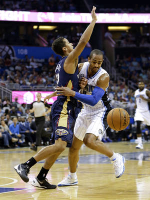 Photo - Orlando Magic's Arron Afflalo, right, momentarily loses the ball after running into New Orleans Pelicans' Brian Roberts during the first half of an NBA basketball game in Orlando, Fla., Friday, Nov. 1, 2013. (AP Photo/John Raoux)