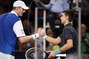 Photo - Novak Djokovic of Serbia, right, greets John Isner of the USA after their round of eight match, at the Paris Masters tennis at Bercy Arena in Paris, France, Thursday, Oct. 31, 2013. Djokovic won the match 7-6, 6-1, 6-2.(AP Photo/Francois Mori)