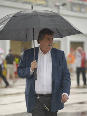 Photo - Mike Helton, president of NASCAR walks through the garages during a rain shower prior to the Sprint Cup series auto race at Daytona International Speedway in Daytona Beach, Fla., Saturday, July 5, 2014. (AP Photo/Phelan M. Ebenhack)