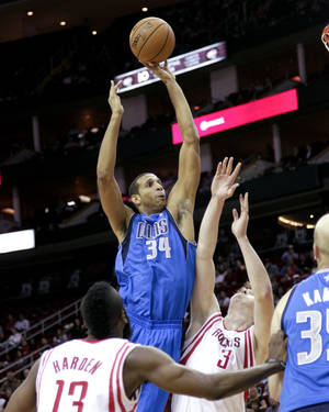 Photo - Dallas Mavericks' Brandan Wright (34) shoots over Houston Rockets' Omer Asik (3) during the first half of an NBA basketball game, Saturday, Dec. 8,  2012, in Houston. (AP Photo/Bob Levey)