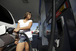 Photo -   In this Feb. 17, 2012 photo, Deborah Aguila fills up her car at a gas station, in San Diego. Retail gasoline prices jumped 3 cents to a national average of $3.61 a gallon, Thursday, Feb. 23, 2012. (AP Photo/Gregory Bull)