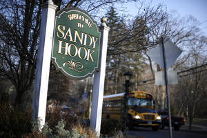 Photo - A bus drives past a sign reading Welcome to Sandy Hook, Wednesday, Dec. 4, 2013, in Newtown, Conn. The 911 calls from the Sandy Hook Elementary School shootings released Wednesday show town dispatchers urged panicked callers to take cover, mobilized help and asked about the welfare of the children as the boom of gunfire could be heard at times in the background. The recordings are released under court order after a legal challenge from The Associated Press. (AP Photo/Jessica Hill)