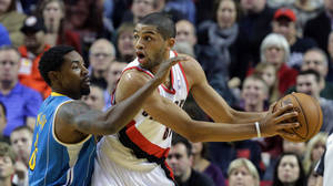 photo - Portland Trail Blazers forward Nicolas Batum, right, from France, looks for help as New Orleans Hornet guard Roger Mason, Jr., defends during the first quarter of an NBA basketball game in Portland, Ore., Sunday, Dec. 16, 2012.(AP Photo/Don Ryan)