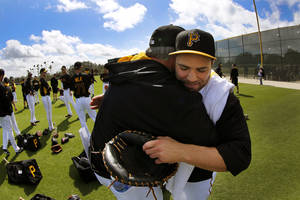 Photo - Pittsburgh Pirates manager Clint Hurdle, left, hugs catcher Russell Martin, right, as he arrives for the team's first day of baseball spring training for pitchers and catchers, in Bradenton, Fla., Thursday, Feb. 13, 2014. (AP Photo/Gene J. Puskar)