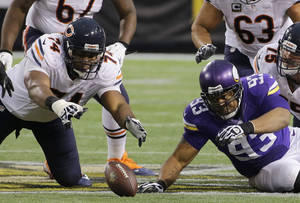 Photo - Chicago Bears tackle Jermon Bushrod, left, and Minnesota Vikings defensive tackle Kevin Williams, right, eye a fumble during the fourth quarter of an NFL football game on Sunday, Dec. 1, 2013, in Minneapolis. The Vikings won 23-20 in overtime. (AP Photo/Ann Heisenfelt)