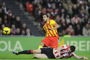 Photo - Barcelona's Martin Montoya, top, duels for the ball with Athletic Bilbao's Kike Sola during their Spanish League soccer match at San Mames stadium in Bilbao, Spain, Sunday, Dec. 1, 2013. (AP Photo/Alvaro Barrientos)