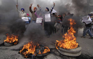 In this Sunday, Feb. 2, 2014 file photo, Indian Sikh protesters shout slogans and burn tires during a protest against Congress party leader Rahul Gandhi for his recent remark on the country's 1984 anti-Sikh riots, in Jammu, India. India has blocked the release of a film on the assassination of former Indian Prime Minister Indira Gandhi, Rahul's grandmother, saying it glorifies her killers and could trigger violent protests, officials said Friday, Aug. 22, 2014. India's film certification board said the film glorified the two Sikh bodyguards who killed Gandhi to avenge her suppression of an insurgency that culminated in an army assault on the Golden Temple, Sikhism's holiest shrine. (AP Photo/Channi Anand, File)
