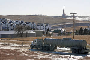 Photo - FILE - In this Feb. 26, 2014, file photo, an oil truck sits in a dirt lot near a new housing development in Watford City, N.D. The United States is still growing older, but the trend is reversing in the Great Plains, thanks to a liberal application of oil.  (AP Photo/Martha Irvine)