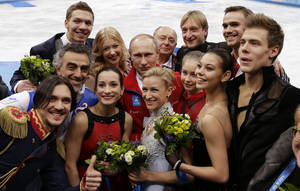 Photo - Russian President Vladimir Putin, centre back, poses for a photograph with the Russian team after they placed first in the team figure skating competition at the Iceberg Skating Palace during the 2014 Winter Olympics, Sunday, Feb. 9, 2014, in Sochi, Russia. (AP Photo/David J. Phillip )