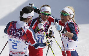 Photo - Norway's gold medal winner Marit Bjoergen, left,  congratulates Norway's bronze medal winner Kristin Stoermer Steira and Norway's silver medal winnerTherese Johaug, right, after the women's 30K cross-country race at the 2014 Winter Olympics, Saturday, Feb. 22, 2014, in Krasnaya Polyana, Russia. (AP Photo/Matthias Schrader)