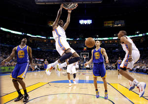 Photo - Kevin Durant, center, dunks the ball between Golden State's Ekpe Udoh, right, and Stephen Curry during OKC's win Tuesday.  PHOTO BY BRYAN TERRY, THE OKLAHOMAN