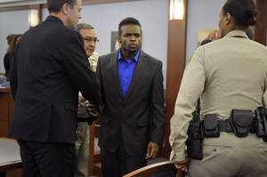 "Photo - Jason Omar Griffith, center, blows a kiss to his mother before being lead away and after a guilty verdict was read during his murder trial at the Regional Justice Center on Thursday, May 22, 2014, in Las Vegas. Griffith was convict of second degree murder of his girlfriend and Luxor ""Fantasy"" dancer Deborah Flores Narvaez in December 2010. (AP Photos/Las Vegas Review-Journal, David Becker)"