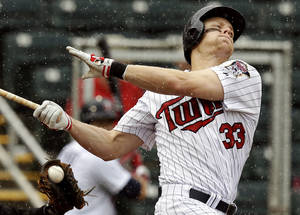 Photo - Minnesota Twins Justin Morneau swings and misses for a strike against Miami Marlins starting pitcher Nate Eovaldi in the fifth inning of an exhibition spring training baseball game in Fort Myers, Fla., Monday, March 18, 2013. (AP Photo/Elise Amendola)