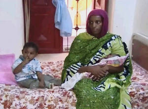 Photo - In this image made from an undated video provided Thursday, June 5, 2014, by Al Fajer, a Sudanese nongovernmental organization, Meriam Ibrahim, sitting next to Martin, her 18-month-old son, holds her newborn baby girl that she gave birth to in jail last week, as the NGO visits her in a room at a prison in Khartoum, Sudan. The Sudanese woman sentenced to death for refusing to recant her Christian faith after allegedly converting from Islam has appealed the sentence, her lawyer said. (AP Photo/Al Fajer)