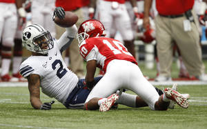 Photo - BYU's Cody Hoffman (2) is tackled by Houston's Zach McMillian (10) during the first half of an NCAA college football game, Saturday, Oct. 19, 2013 in Houston. (AP Photo/Eric Christian Smith)