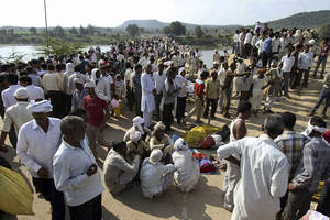 Photo - Indian villagers gather after a deadly stampede on a bridge across the Sindh River in Datia district in Madhya Pradesh state, India, Sunday, Oct. 13, 2013. A stampede by masses of Hindu worshippers left scores of people dead on a bridge they had been crossing to reach a temple in central India, police said. (AP Photo)