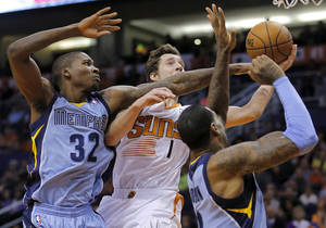 Photo - Phoenix Suns' Goran Dragic (1), of Slovenia, drives against Memphis Grizzlies' Ed Davis (32) and James Johnson during the second half of an NBA basketball game on Thursday, Jan. 2, 2014, in Phoenix. The Grizzlies won 99-91.(AP Photo/Matt York)